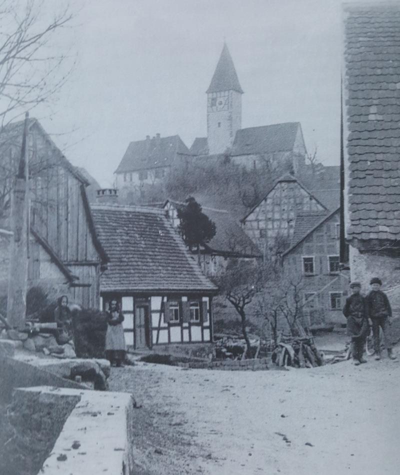 Die beiden Buben stehen vor dem Anwesen Bach, das heute zum Rathaus umgebaut wurde. Der Holzbrunnen ganz links gehört zu Haus Nr. 12.